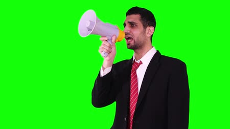 gritante : Young Caucasian businessman announcing news with a megaphone in the studio while standing against green screen background