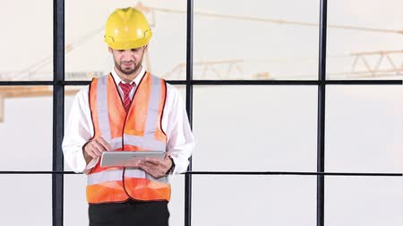 stavitel : Male Caucasian contractor working with tablet computer while wearing helmet, safety vest, and standing near the window with a crane background