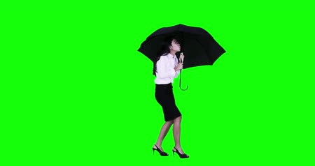 önlemek : Worried businesswoman standing in the studio while protecting herself with an umbrella with green screen background. Shot in 4k resolution Stok Video