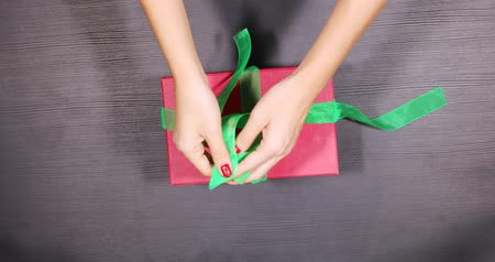 stuha : Top view of unrecognizable woman hands wrapping a Christmas gift and decorate it with a ribbon on the wooden table. Shot in 4k resolution