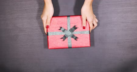 holding : Top view of anonymous woman hands giving a presents box on the wooden table. Shot in 4k resolution Stock Footage