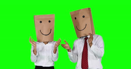 atenção : Anonymous businesspeople with paper bag on their head, clapping hands and showing thumb up in the studio with green screen background. Shot in 4k resolution