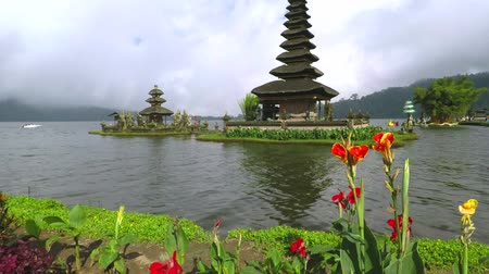 kultúra : Stunning view footage of Ulun Danu Bratan Temple with flowers and cloudy sky in Tabanan, Bali, Indonesia.