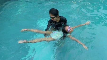 lesson : Young mother teaching her daughter to swim while wearing swimsuit at pool
