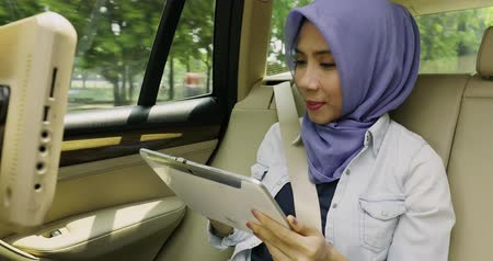 ислам : Young muslim woman using a digital tablet while wearing a veil in the car, shot in 4k resolution