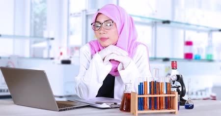 laboratorní plášť : Female muslim scientist working and smiling in the laboratory with a laptop and test tube on the table, shot in 4k resolution