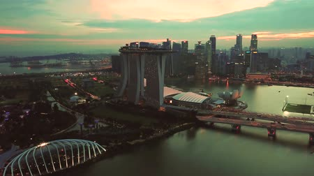 baía : Singapore. November 21, 2017: Stunning aerial footage of Marina Bay Sands Hotel Singapore and Gardens by the Bay at dusk time. Shot in 4k resolution