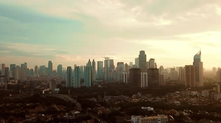 felhőkarcoló : JAKARTA - Indonesia. January 23, 2018: Beautiful aerial landscape of skyscrapers near residential houses from a drone flying down in Jakarta city. Shot in 4k resolution