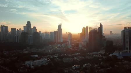 felhőkarcoló : Beautiful aerial footage of Jakarta city at sunset time with silhouette of skyscrapers from a drone flying down. Shot in 4k resolution Stock mozgókép