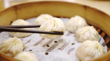 dimsum : Closeup of hot steamed chinese dim sum on steamer with chopsticks, shot in the restaurant