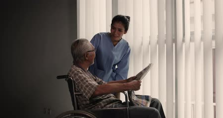 caregiver : Old man sitting on wheelchair and pushed by his assistance or nurse after reading a newspaper near the window. Shot in 4k resolution