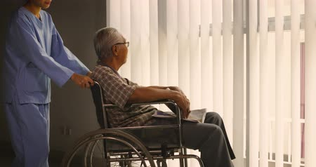 pushed : Old man sitting on wheelchair, pushed by his nurse towards the window to read a newspaper. Shot in 4k resolution
