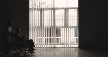 pushed : Silhouette of elderly man sitting on wheelchair and pushed by his nurse near the window at home. Shot in 4k resolution