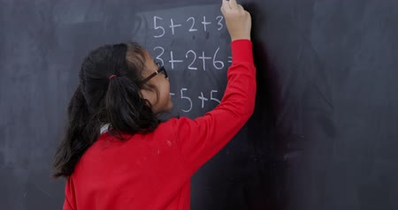 obter : Video footage of a smart female elementary school student thinks before answer a math problem on the blackboard in the classroom. Shot in 4k resolution