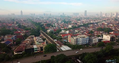 passagem elevada : Beautiful aerial view of Jakarta downtown with background of flyover, railroad, and crowded residential houses. Recorded from a drone. Shot in 4k resolution
