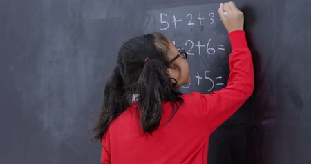 tablica : Happy female elementary school student solving a math problem on the blackboard and showing thumbs up in the classroom. Shot in 4k resolution