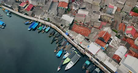 urban landscape : Aerial landscape of fishing village with fishing boats and slum houses settlement near the Sunda Kelapa port in North Jakarta, Indonesia. Shot in 4k resolution