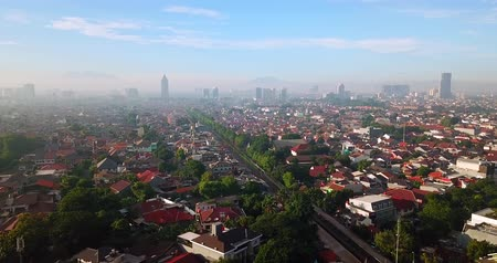 central business district : Beautiful aerial landscape of crowded residential houses and railway from a drone flying forward on misty morning in Jakarta city, Indonesia. Shot in 4k resolution Stock Footage
