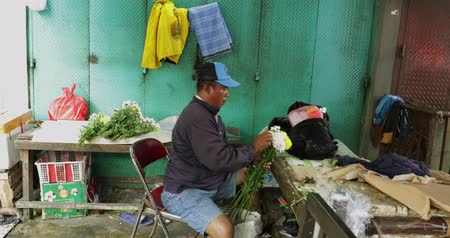 trimmelés : JAKARTA - Indonesia. March 28, 2018: Male florist making a bouquet in his stall at traditional market in Jakarta city. Shot in 4k resolution Stock mozgókép