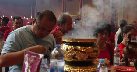 myrrh : JAKARTA - Indonesia. March 26, 2018: Crowded buddhist people praying with incense pot in the Vihara Dharma Bhakti at Glodok, Jakarta. Shot in 4k resolution