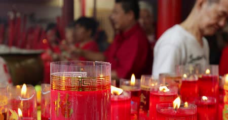 myrrh : JAKARTA - Indonesia. March 26, 2018: Closeup of burning red candles with buddhist people background on Chinese New Year celebration in Chinese temple. Shot in 4k resolution