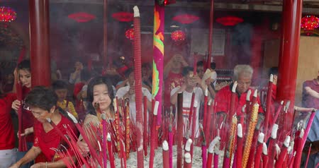 ладан : JAKARTA - Indonesia. March 26, 2018: Crowded buddhist people celebrating Chinese New Year by praying with burning incense sticks in Vihara Dharma Bhakti. Shot in 4k resolution