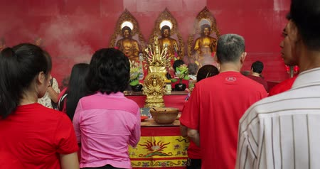 myrrh : JAKARTA - Indonesia. March 26, 2018: Buddhist people celebrating Chinese New Year by praying in front of Buddha statue at the Vihara Dharma Bhakti. Shot in 4k resolution