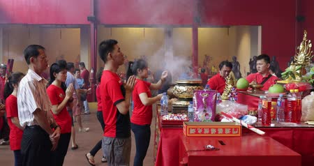 ладан : JAKARTA - Indonesia. March 26, 2018: Buddhist people celebrating Chinese New Year by praying and doing ritual with incense pot in the temple. Shot in 4k resolution Стоковые видеозаписи