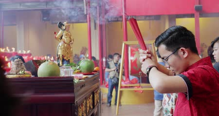myrrh : JAKARTA - Indonesia. March 28, 2018: Young Chinese man praying with incense sticks on Chinese New Year celebration at Chinese temple in Glodok, Jakarta. Shot in 4k resolution