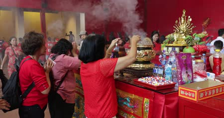 myrrh : JAKARTA - Indonesia. March 26, 2018: Woman celebrating Chinese New Year by praying and doing ritual with incense pot in Vihara Dharma Bhakti at Glodok, Jakarta. Shot in 4k resolution