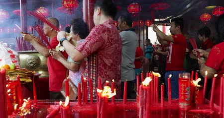 ритуал : JAKARTA - Indonesia. March 26, 2018: Buddhist people praying with burning incense sticks on Chinese New Year celebration at Jin De Yuan temple, Glodok, Jakarta. Shot in 4k resolution
