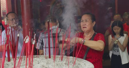 myrrh : JAKARTA - Indonesia. March 26, 2018: Female buddhist worshiping on Chinese New Year while holding incense sticks in Jin De Yuan Temple at Glodok, Jakarta. Shot in 4k resolution