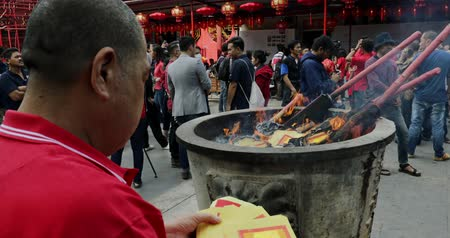myrrh : JAKARTA - Indonesia. March 28, 2018: Chinese man burning paper money on the incense pot at Chinese New Year celebration in Chinatown of Glodok, Jakarta city. Shot in 4k resolution