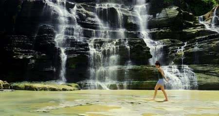západ : Happy woman enjoying holiday and her freedom at beautiful Cigangsa waterfall, Sukabumi, West Java, Indonesia. Shot in 4k resolution Dostupné videozáznamy