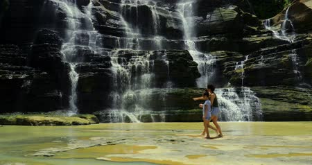 punto : Feliz madre y su hija abrazando junto con hermoso fondo de cascada Cigangsa en Sukabumi, Java Occidental, Indonesia. Disparo en resolución 4k