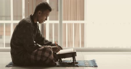 holy book : Young muslim man reading Quran on the wooden stand while wearing muslim clothes at home. Shot in 4k resolution