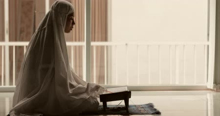 holy book : Young muslim woman reading Quran on the wooden stand near the window at home. Shot in 4k resolution Stock Footage