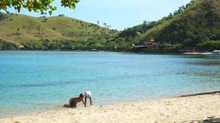 Флорес : Two siblings enjoying holiday by playing and seek something on the seashore in Komodo Island near Bali, Indonesia