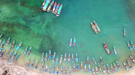 západ : Beautiful aerial shot of traditional fisherman boats anchoring in a row at ujung Genteng beach, Sukabumi, West Java, Indonesia