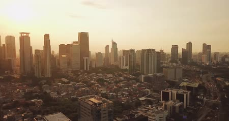central business district : JAKARTA - Indonesia. April 11, 2018: Panoramic aerial landscape of Jakarta downtown with modern buildings on sunset time from a drone. Shot in 4k resolution Stock Footage