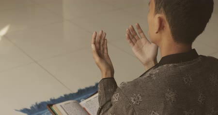 holy book : Male muslim praying to the GOD while lifting his hands after reading Quran at home. Shot in 4k resolution