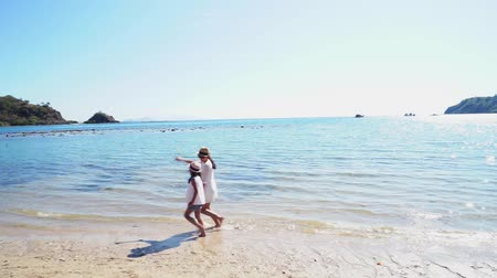 Флорес : Happy mother and her daughter running on the tropical beach with white sand while holding hands together in Komodo Island near Bali, Indonesia