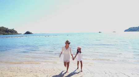 Флорес : Happy little girl and her mother enjoying holiday by running on the beach while holding hands in Komodo Island near Bali, Indonesia Стоковые видеозаписи