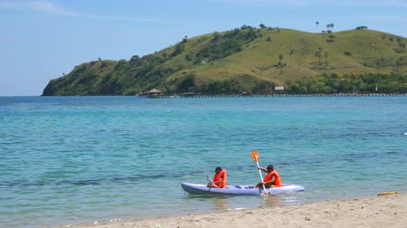 Флорес : Two happy children enjoying holiday by kayaking together on the Labuan Bajo beach, East Nusa Tenggara near Bali, Indonesia