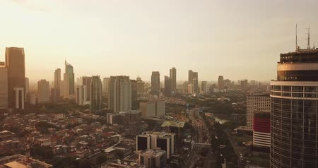 central business district : JAKARTA - Indonesia. April 11, 2018: Panoramic aerial view of Jakarta capital city with modern buildings at sunset time from a drone. Shot in 4k resolution Stock Footage