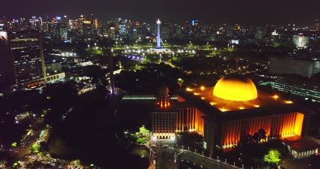 worship : Beautiful aerial landscape of National Monument and Istiqlal mosque with sparkle night lights in Jakarta city, Indonesia. Shot in 4k resolution