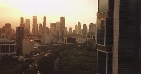 para a frente : JAKARTA - Indonesia. April 11, 2018: Beautiful aerial panorama of Jakarta central business district with modern office buildings on sunset time. Shot in 4k resolution Vídeos