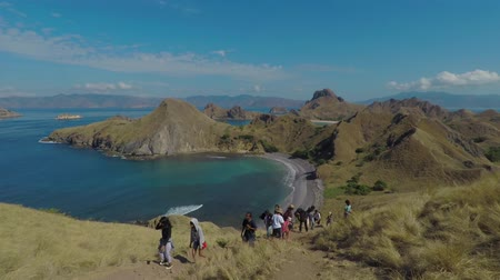 Флорес : Padar Island - Indonesia. April 16, 2018: People hiking on the Padar Island with beautiful landscape, East Nusa Tenggara, Indonesia Стоковые видеозаписи