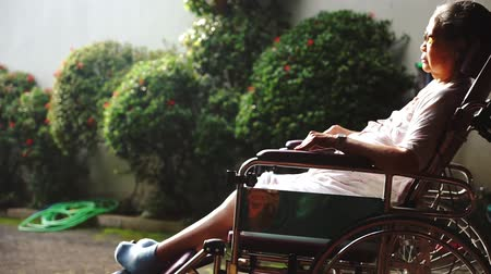 oneself : Paralyzed old woman sunbathing for health on the morning while sitting on the wheelchair at nursing home Stock Footage