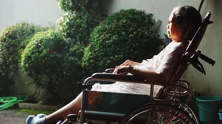 oneself : Elderly woman with paralysis disease sitting on wheelchair while sunbathing for health on the morning at home